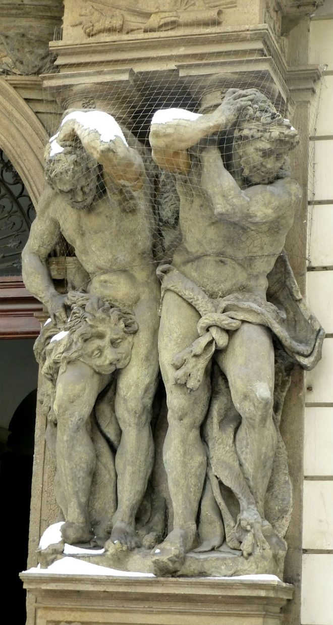 Two statues holding a balcony